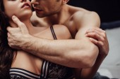 Photo cropped view of man passionately touching neck of sexy woman isolated on black