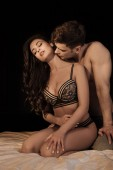 Photo shirtless man kissing beautiful seductive woman in bed isolated on black