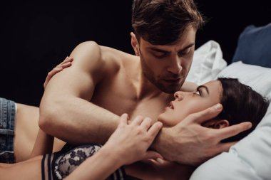 handsome man gently embracing beautiful woman in bed isolated on black