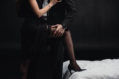 cropped view of man touching woman in stockings isolated on black