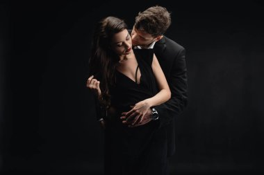 passionate young couple in formal wear kissing isolated on black