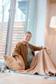cheerful man sitting on floor by large window at new home