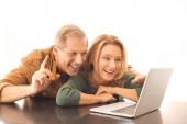 usmívající se muž ukazuje znamení myšlenka při používání notebooku s manželkou na bílém pozadí