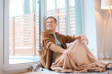 Happy man sitting on floor under soft fleece blanket and looking through large window stock vector