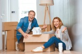 izgatott boldog pár ház modell mutatja kartondobozban Kibontás közben