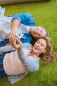 selective focus of happy couple holding keys with house model trinket while lying on green carpet