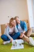 šťastný pár objímání při posezení na zelený koberec poblíž domu modelu