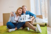 Photo happy couple hugging and demonstrating house model while sitting on floor on green carpet