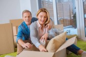 happy couple unpacking carton boxes at new home