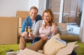 Photo happy couple clinking glasses of white wine while sitting by cardboard boxes