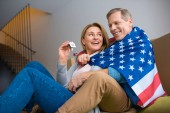 happy woman holding keys with house model trinket while wrapping in usa national flag with husband