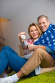 selective focus of happy woman holding keys with house model trinket while wrapping in usa national flag with husband