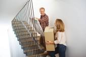 Fotografie žena s krabici a muž s obrázkem jít nahoru