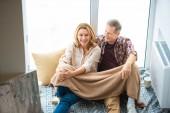 glückliches Paar sitzt am Boden, die durch große Fenster im neuen Zuhause