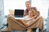 usmívající se žena zobrazeno laptop s černou obrazovkou při odpočinku na podlahu velké okno spolu s manželem
