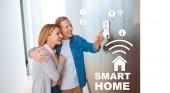 šťastný manžel pÛdû ženu, zatímco ukazuje na ovládací panel systém inteligentního domu
