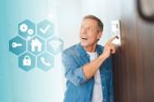 Happy pohledný muž pomocí ovládacího panelu systém inteligentního domu