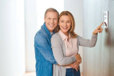 smiling husband hugging wife pointing at smart home control panel