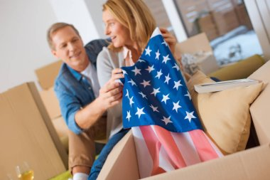 selective focus of woman getting usa flag out of cardboard box