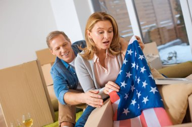 surprised woman getting usa flag out of cardboard box while sitting near smiling husband at new home
