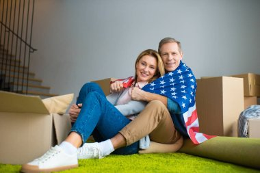 happy couple wrapping in usa national flag and looking at camera