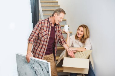 smiling man holding picture while standing near wife sitting on stairs and unpacking carton box
