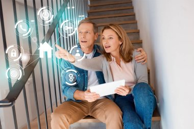 wife pointing hand while sitting with husband on stairs and using digital tablet, smart home concept