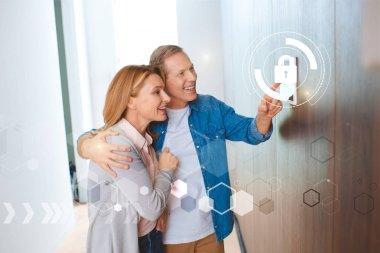 Smiling husband pointing at smart house system control panel and hugging happy wife stock vector