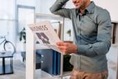 oříznutý pohled veselý podnikatel stojící a čtení obchodní noviny v moderní kanceláři