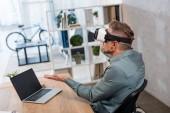 virtuális-valóság sisak viselése ülve laptop-val üres képernyő közelében üzletember
