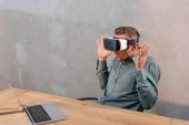 Fotografie schockierter Geschäftsmann trägt Virtual-Reality-Headset, während er in der Nähe von Laptop im Büro sitzt