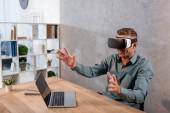 Geschäftsmann, tragen von virtual-Reality-Kopfhörer beim Sitzen im Büro in der Nähe von laptop