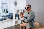 fröhlicher Geschäftsmann mit Virtual-Reality-Headset beim American Football