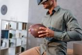 abgeschnittene Ansicht eines lächelnden Geschäftsmannes mit Virtual-Reality-Headset und American Football in der Hand