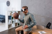businessman wearing virtual reality headset and holding basketball in modern office