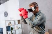 Fotografie ernsthaften Geschäftsmann tragen von virtual-Reality-Kopfhörer und Boxhandschuhe im Büro