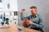 Fotografie fröhliche Geschäftsmann hält Basketball Championship am Laptop im Büro beobachten