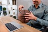 Fotografie Ausgeschnittene Ansicht eines gut gelaunten Geschäftsmannes, der Basketball hält, während er die Meisterschaft auf seinem Laptop im Büro verfolgt