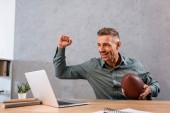 Fotografie fröhliche Geschäftsmann gerade Meisterschaft auf Laptop und american-Football in modernen Büros halten