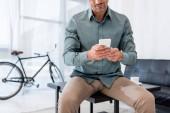 levágott nézet üzletember dohányzóasztal ült, és használ smartphone