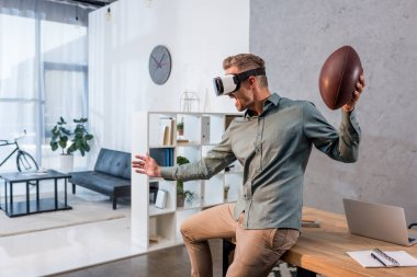 happy businessman wearing virtual reality headset and holding american football