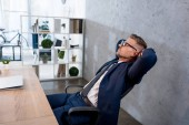 handsome businessman in glasses relaxing near laptop in office