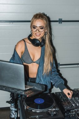 attractive dj woman in glasses and headphones looking at laptop while touching dj mixer