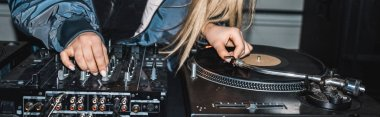 panoramic shot of dj woman standing near dj mixer and vinyl record