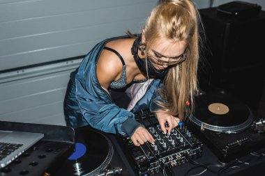 focused dj woman touching dj mixer and standing near vinyl records