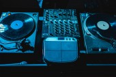 Photo dj mixer with equalizer and vinyl records in nightclub