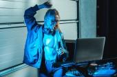 donna attraente ed elegante dj in occhiali ballo vicino al computer portatile