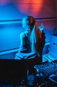 Fotografie  blonde dj woman gesturing while standing in nightclub