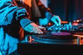 selective focus of dj woman touching vinyl record in nightclub
