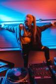 attractive blonde dj girl in glasses standing near dj mixer in nightclub